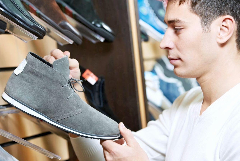 парень выбирает обувь