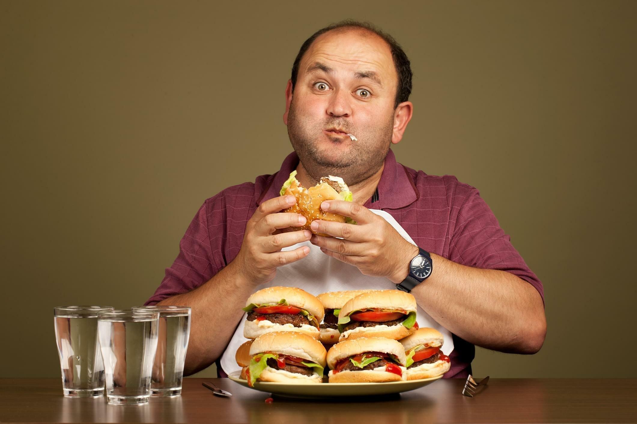 мужчина с лишним весом ест бургеры